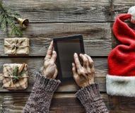 Concezione: Preparazione dei regali di Natale Un uomo tiene un PC della compressa in sue mani ed imballa i regali di Natale Fotografie Stock Libere da Diritti