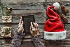 Concezione: Preparazione dei regali di Natale Un uomo tiene un PC della compressa in sue mani ed imballa i regali di Natale Fotografie Stock