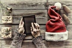 Concezione: Preparazione dei regali di Natale Un uomo tiene un PC della compressa in sue mani ed imballa i regali di Natale Immagine Stock