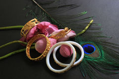 Conch bangle and gold bracelet with pink lotus and peacock feather  on black background. Royalty Free Stock Photography