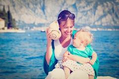 Concha do mar de escuta da mãe e da filha pequena Fotografia de Stock