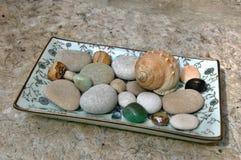 Concha marina, guijarros y piedras preciosas en la placa Fotografía de archivo libre de regalías