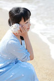 Concha marina que escucha de la mujer japonesa joven Imagen de archivo