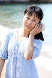 Concha marina que escucha de la mujer japonesa joven Imagenes de archivo