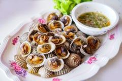 Conchas de peregrino asadas en la placa blanca con la salsa de mariscos imagen de archivo