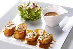 Conchas de peregrino con la ensalada y la salsa Imagen de archivo libre de regalías