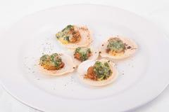 Conchas de peregrino de la tostada con queso y espinaca Foto de archivo