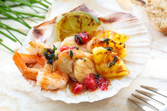 Conchas de peregrino fritas con la fruta y los camarones asados a la parrilla Imagenes de archivo