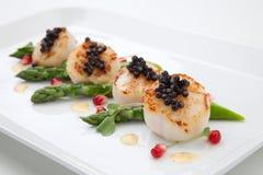 Conchas de peregrino y caviar negro Foto de archivo