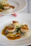 Conchas de peregrino y raviolis del gastrónomo con la salsa en un blanco Foto de archivo libre de regalías