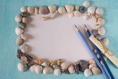 Conchas do mar com as folhas de papel e a pena em um fundo azul Fotografia de Stock