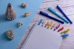 Conchas do mar em um fundo azul, em umas folhas do Livro Branco com Pegs coloridos e em umas penas em uma tabela de madeira Conce fotografia de stock