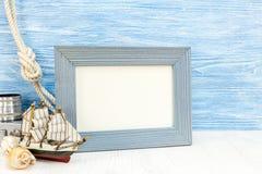 Conchas marinas con el velero y el marco vacío de la foto en el CCB de madera azul Fotos de archivo libres de regalías