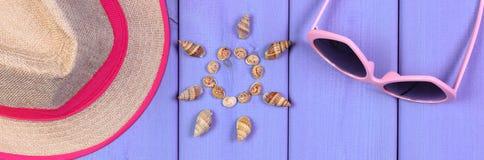 Conchas marinas en la forma del sol, de gafas de sol y del sombrero de paja en los tableros púrpuras, accesorios para el verano Imagen de archivo