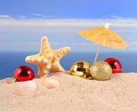 Conchas marinas y estrellas de mar de las decoraciones de la Navidad en una arena de la playa Imágenes de archivo libres de regalías