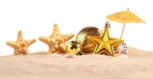 Conchas marinas y estrellas de mar de las decoraciones de la Navidad en una arena de la playa encendido Imágenes de archivo libres de regalías