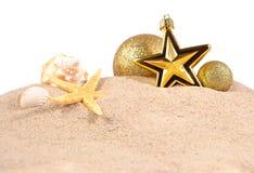 Conchas marinas y estrellas de mar de las decoraciones de la Navidad en una arena de la playa encendido Foto de archivo