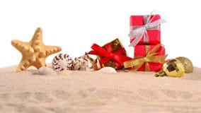 Conchas marinas y estrellas de mar de las decoraciones de la Navidad en una arena de la playa encendido Fotos de archivo