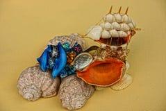 Conchas marinas y un bote pequeño en una sustancia amarilla Fotos de archivo