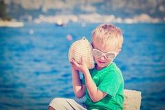 Conchiglia d'ascolto del bambino felice alla spiaggia Fotografia Stock
