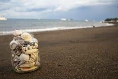 Conchiglie in barattolo sulla spiaggia di sabbia Paesaggio tropicale con il mare e le barche bianche Immagine Stock