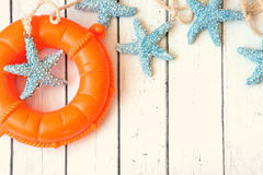Conchiglie decorative di salvagente, dell'ancora e delle stelle marine sopra fondo bianco di legno Immagine Stock