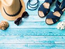 Conchiglie degli occhiali da sole dei sandali dei braccialetti del cappello di paglia del fondo di estate su uno spazio blu della Fotografie Stock Libere da Diritti