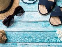 Conchiglie degli occhiali da sole dei sandali dei braccialetti del cappello di paglia del fondo di estate su uno spazio blu della Immagini Stock Libere da Diritti