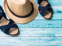 Conchiglie degli occhiali da sole dei sandali dei braccialetti del cappello di paglia del fondo di estate su uno spazio blu della Fotografie Stock