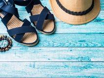 Conchiglie degli occhiali da sole dei sandali dei braccialetti del cappello di paglia del fondo di estate su uno spazio blu della Fotografia Stock