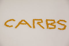 Conchiglie pasta arrange in shape of carbs text. On white background Royalty Free Stock Image