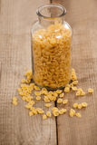 Conchiglie pasta spilled out of glass jar Royalty Free Stock Images