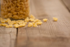 Conchiglie pasta spilled out of glass jar Royalty Free Stock Image