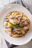 Conchiglie with porcini mushrooms and parmesan close-up. vertica Royalty Free Stock Photos