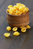 Conchiglioni italian pasta in wood bowl Royalty Free Stock Photos