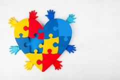Conciencia del autismo de la ayuda de las manos del corazón del rompecabezas fotografía de archivo