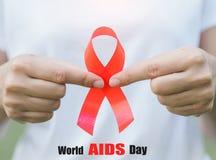 Conciencia roja de la cinta en la mano del adolescente de la muchacha para el Día Mundial del Sida Imagen de archivo libre de regalías