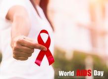 Conciencia roja de la cinta en la mano del adolescente de la mujer para el Día Mundial del Sida Imagenes de archivo