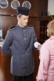 Concierge dans l'hôtel donnant la carte principale à la femme photographie stock libre de droits