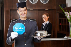 Concierge dans l'hôtel tenant le signe de service Images libres de droits