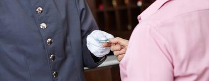 Concierge donnant la carte de chambre d'hôtel à la femme images stock