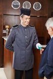 Concierge giving senior man hotel key card Royalty Free Stock Photo