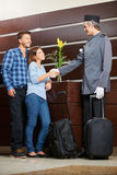 Concierge greeting young couple in hotel royalty free stock images