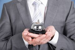 Concierge holding service bell. Concierge in suit holding service bell. Closeup shot Stock Images