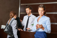 Concierge at hotel reception serving guests. With women checking her smartphone Royalty Free Stock Photo