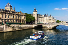 Conciergerie Castle and Seine River with cruise tour boat. Paris. View of the Seine River with cruise tour boat and Conciergerie Castle. Castle Conciergerie is a stock photo
