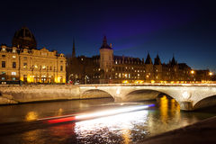 Conciergerie et le Pont de Change at night, Paris. View from the embankment to the Conciergerie et le Pont de Change at night. The 'bateau-mouche' movement is Royalty Free Stock Images