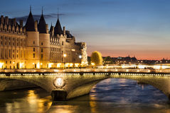Conciergerie by night, Paris, France. View of Paris by night with a bridge over the Seine river and the Conciergerie building near Notre-Dame Royalty Free Stock Photos