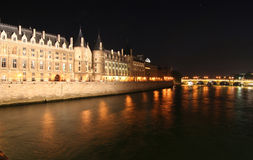 Conciergerie in Paris. Conciergerie and Seine in Paris at night royalty free stock images