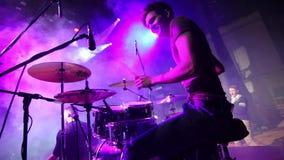 Concierte a la banda de rock que se realiza en etapa con el ejecutante del cantante, guitarra, batería Punky, metal pesado o roca metrajes